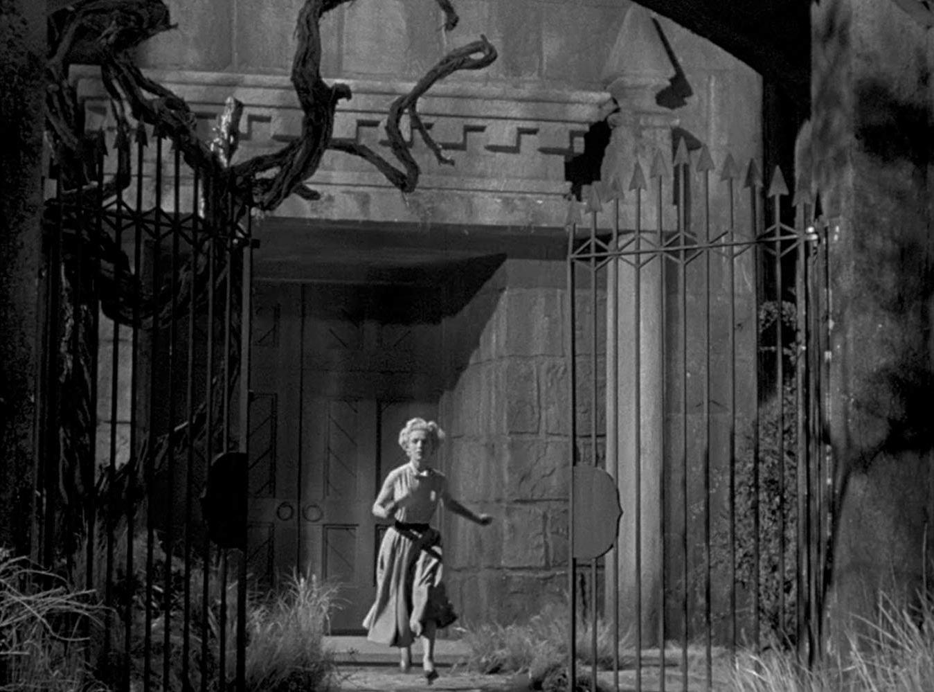 Veronica Hurst runs for the gates of Castle Craven in The Maze (1953)