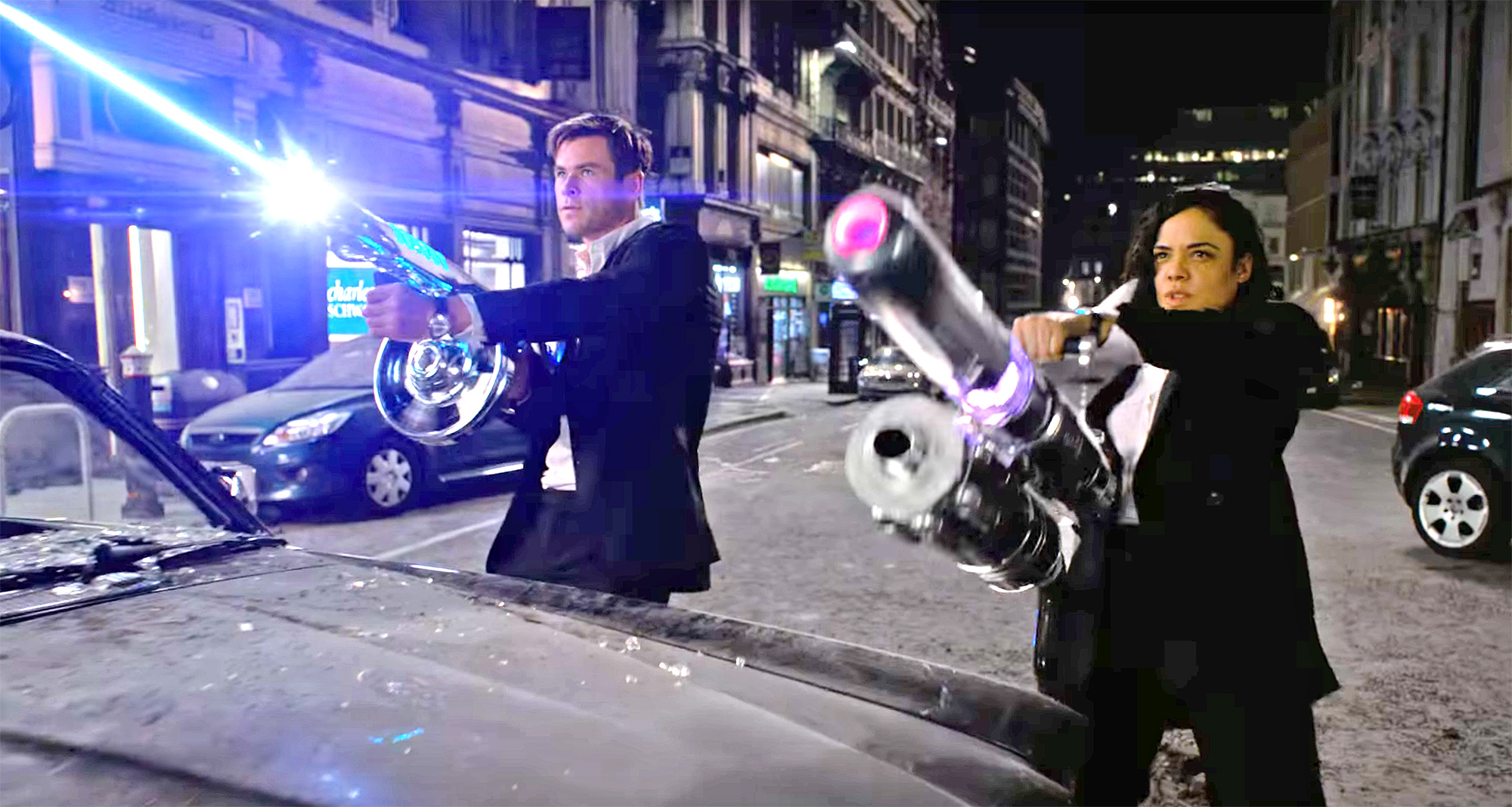 Agents M (Tessa Thompson) and H (Chris Hemsworth) wield weaponry against alien assassins in London in Men in Black: International (2019)