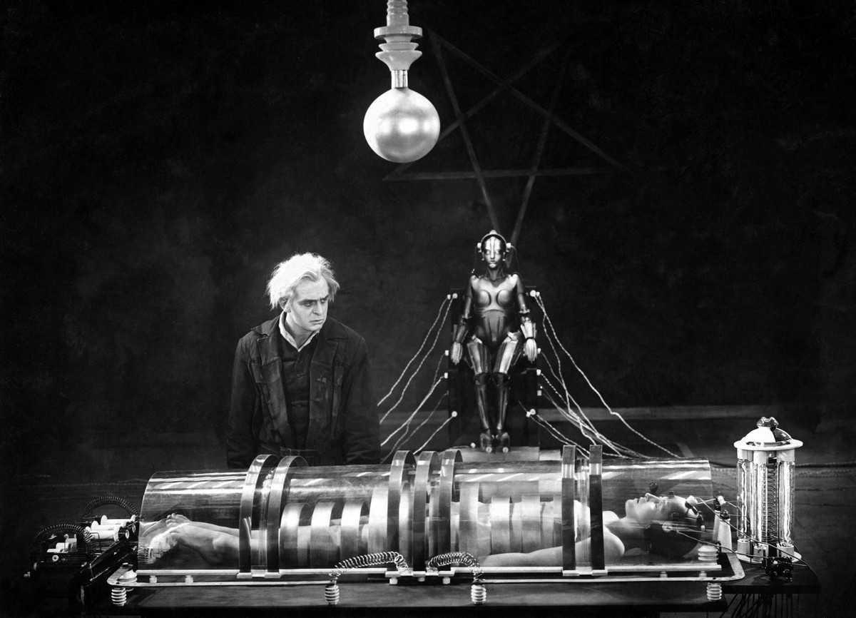 The scientist Rotwang (Rudolf Klein-Rogge) surveys the imprisoned Maria (Brigitte Helm) as he prepares to bring the robot to life in Metropolis (1927)