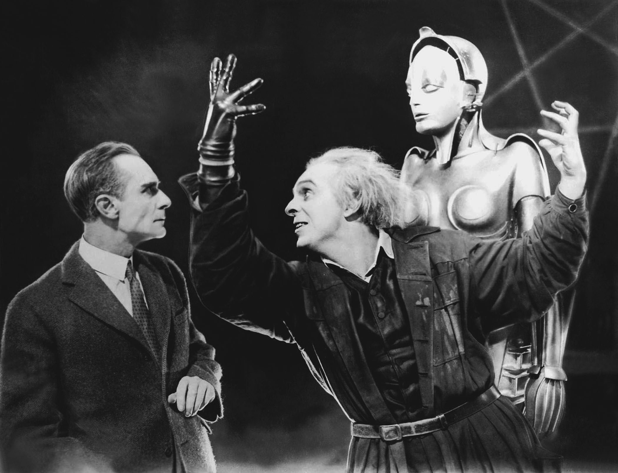 Rotwang (Rudolf Klein-Rogge) remonstrates to Joh Fredersen (Alfred Abel) while the robot Maria (Brigitte Helm) looks on in Metropolis (1927)