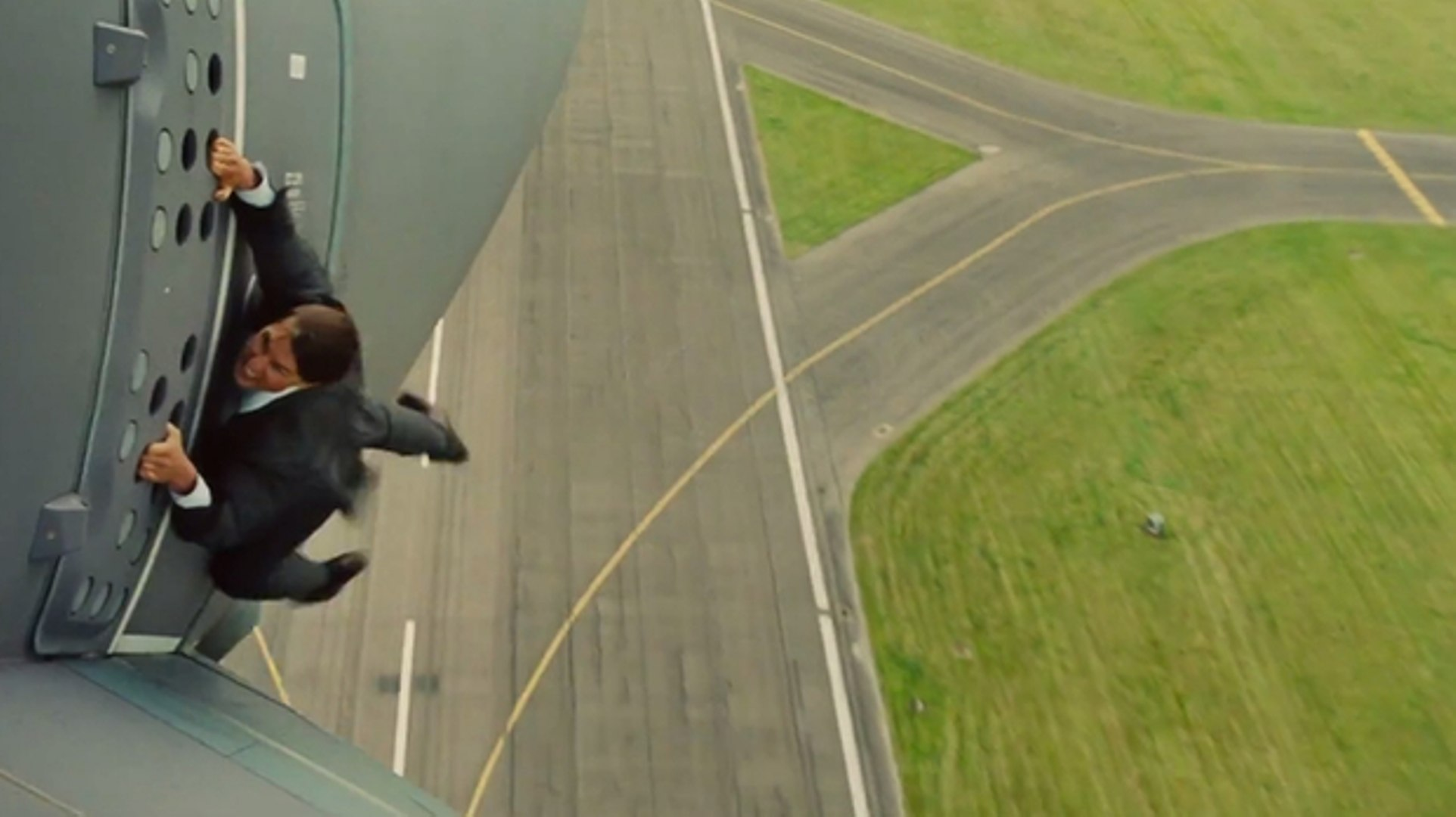 Tom Cruise clinging to the outside of an airplane in Mission: Impossible - Rogue Nation (2015)