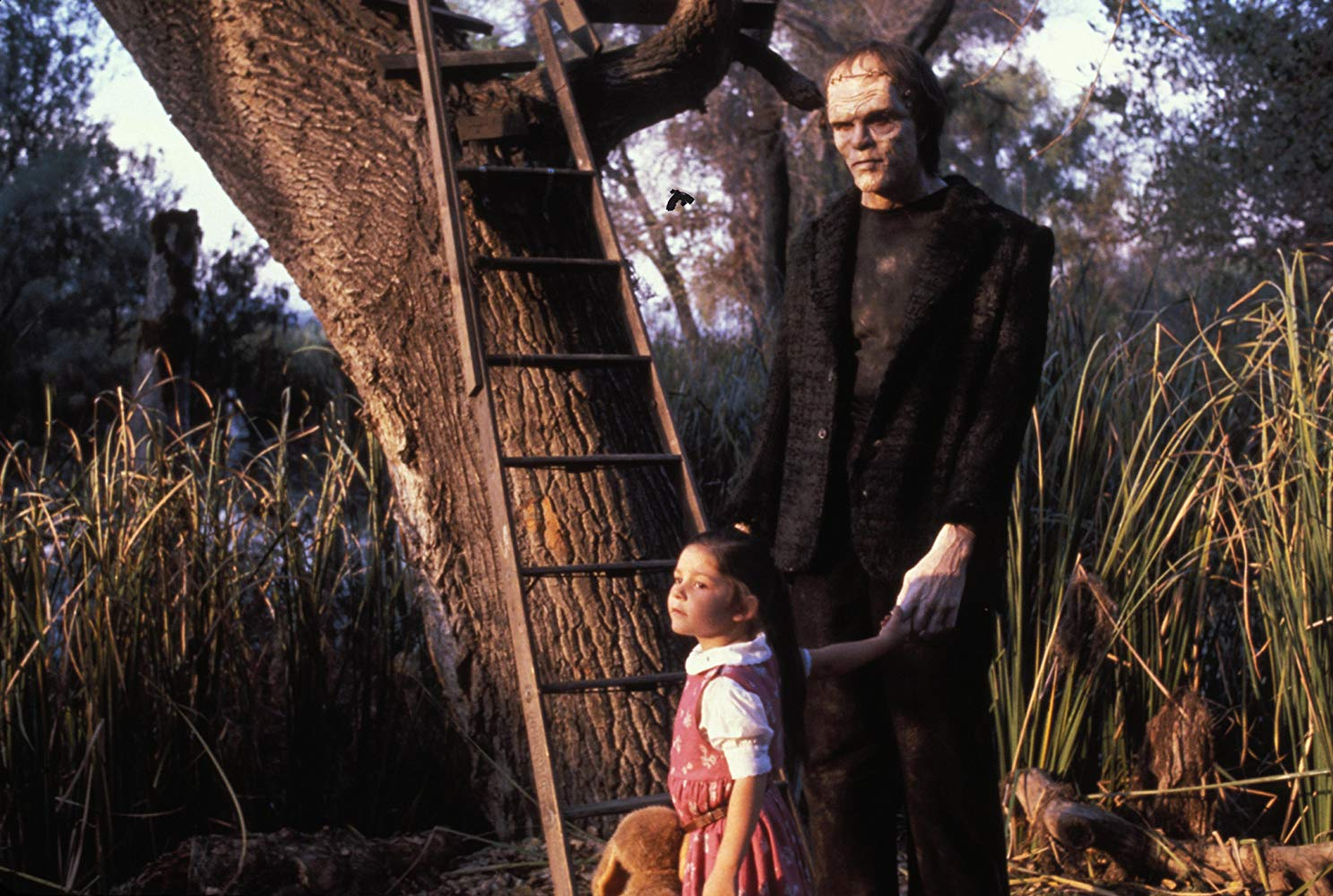 Young Phoebe (Ashley Bank) befriends the Frankenstein monster (Tom Noonan) in The Monster Squad (1987)