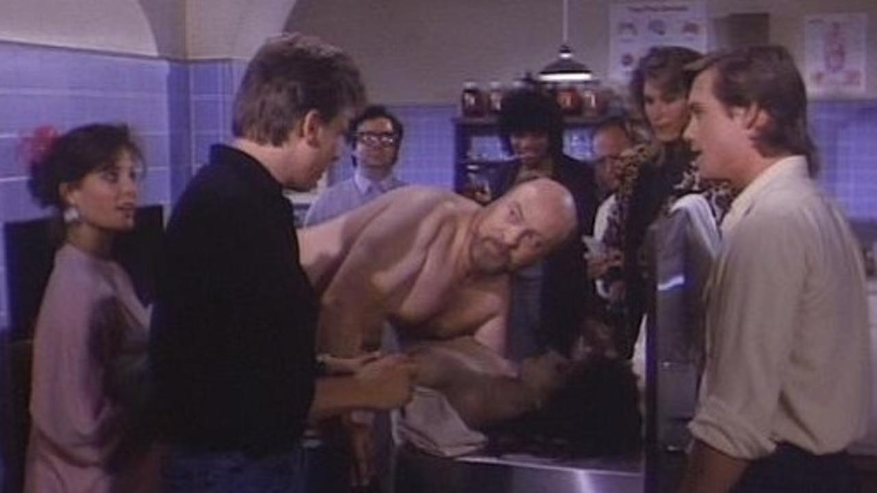 Paul Bartel (c) demonstrates his penchant for necrophilia, flanked by (l to r) Lynn Danielson, Perry Lang (back to camera in black shirt), Mary Woronov (in leopard skin) and Christopher Atkins (to her right) in Mortuary Academy (1988)