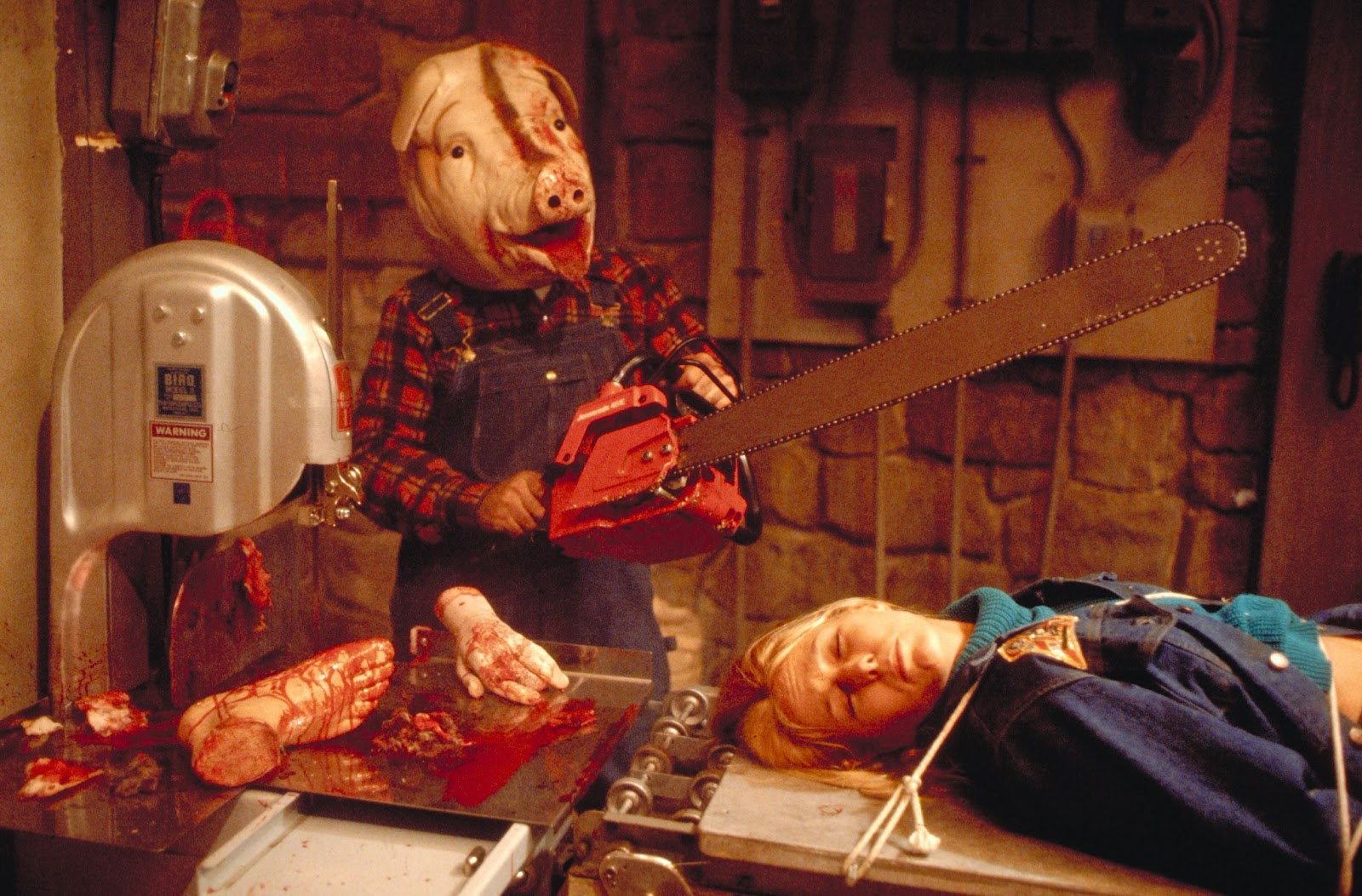 Rory Calhoun (in pig mask) with an imprisoned Nina Axelrod in Motel Hell (1980)
