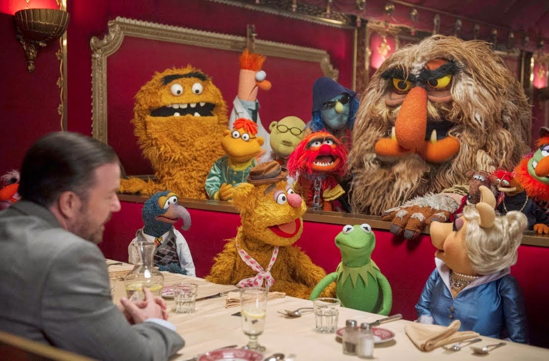 The Muppets sit down in a restaurant with manager Dominic Badguy (Ricky Gervais) in Muppets Most Wanted (2014)