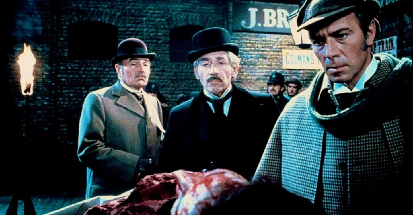 Dr Watson (James Mason) and Inspector Lestrade (Frank Finlay) look on as Sherlock Holmes (Christopher Plummer) examines a body in Murder By Decree (1979)