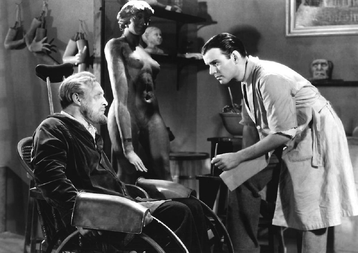 (l to r) The wheelchair-ridden waxworks curator Igor (Lionel Atwill) and his assistant Allen Vincent in Mystery of the Wax Museum (1933)