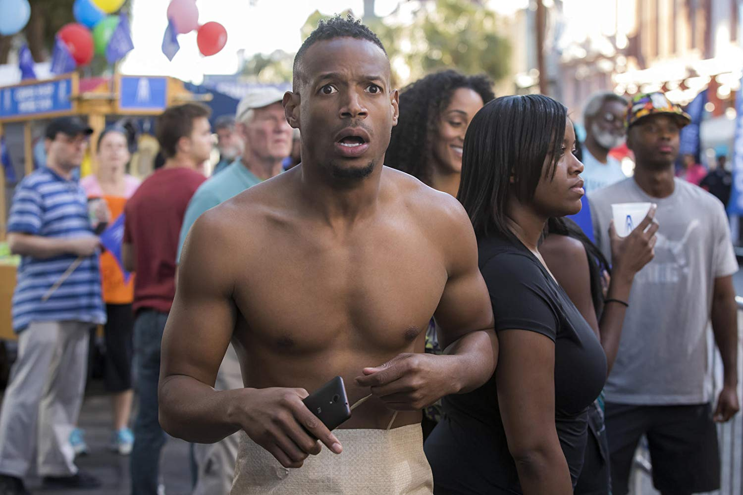 Marlon Wayans forced to make his way through a parade without any clothes in Naked (2017)