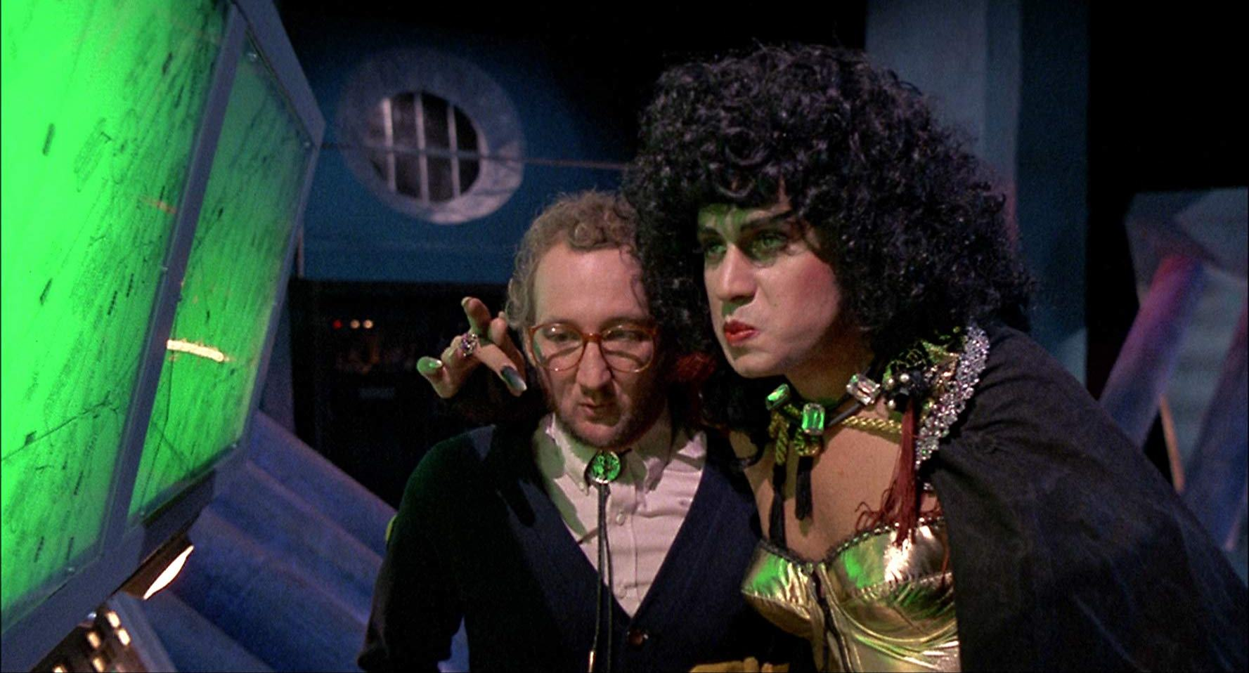 (l to r) Mad scientist Robert Englund and the crossdressing super-villain Velvet Von Ragnar (Gene Simmons) in Never Too Young to Die (1986)