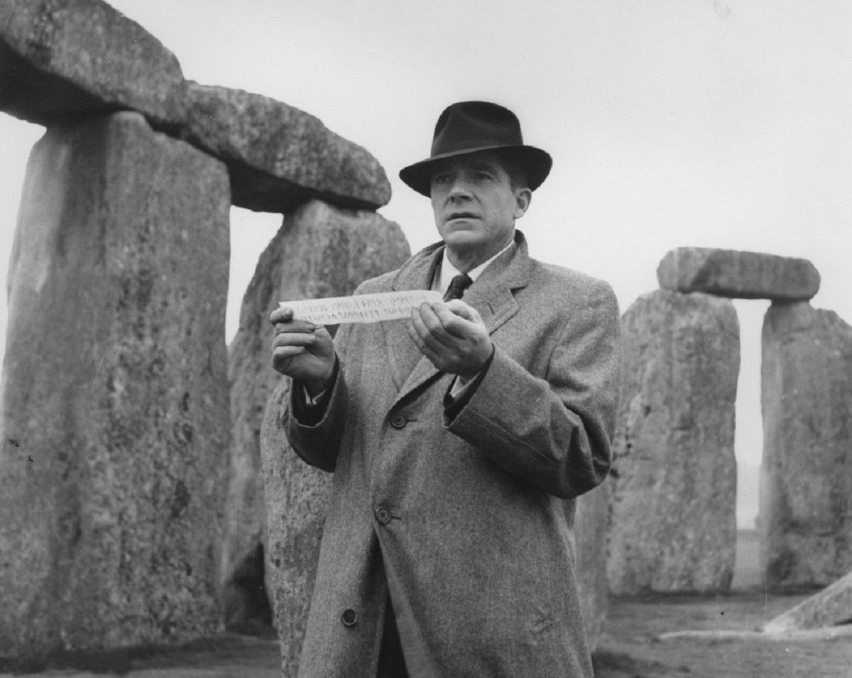 Rationalist hero John Holden (Dana Andrews) receives the rune with Stonehenge in the background in Night of the Demon (1957)
