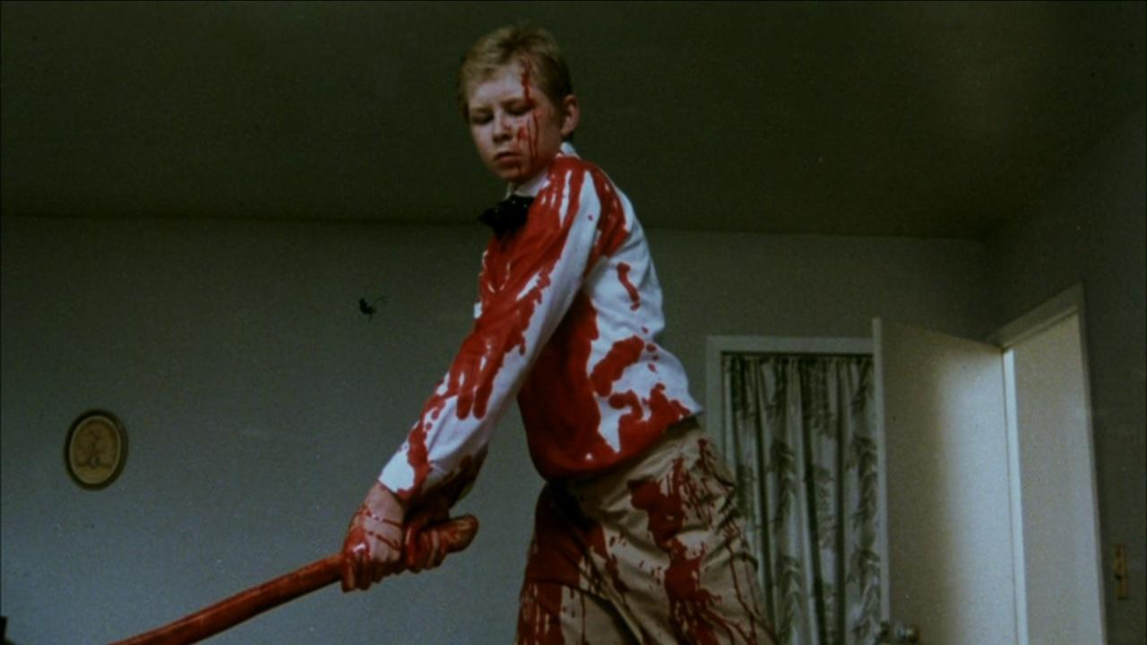 Young George (Scott Praetorius) hacks his parents up with an axe in Nightmares in a Damaged Brain (1981)