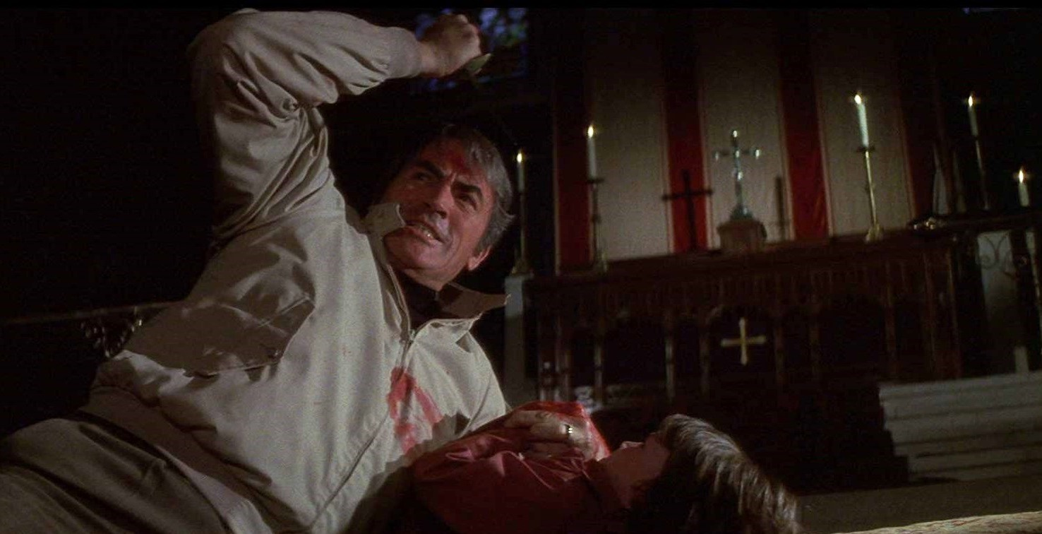 Robert Thorn (Gregory Peck) attempts to kill his son Damien (Harvey Stephens) on the altar of a church in The Omen (1976)