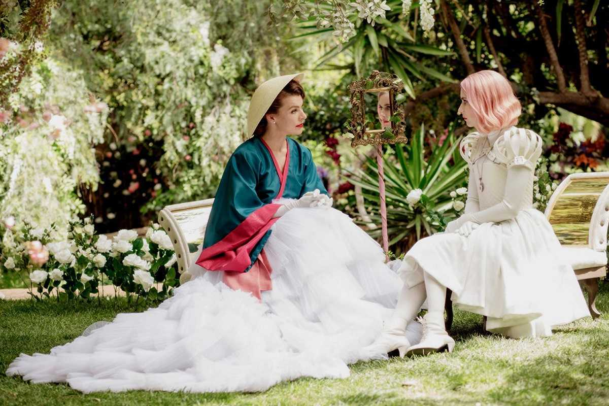 (l to r) The Duchess (Milla Jovovich) gives Uma (Emma Roberts) instruction in Paradise Hills (2019)