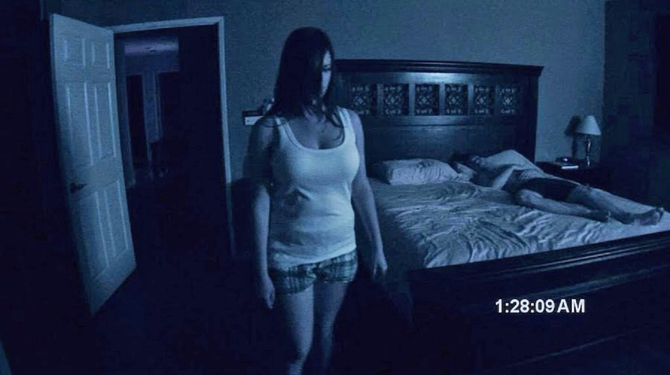 A possessed Katie Featherston stands while Micah Sloat sleeps in Paranormal Activity (2007)