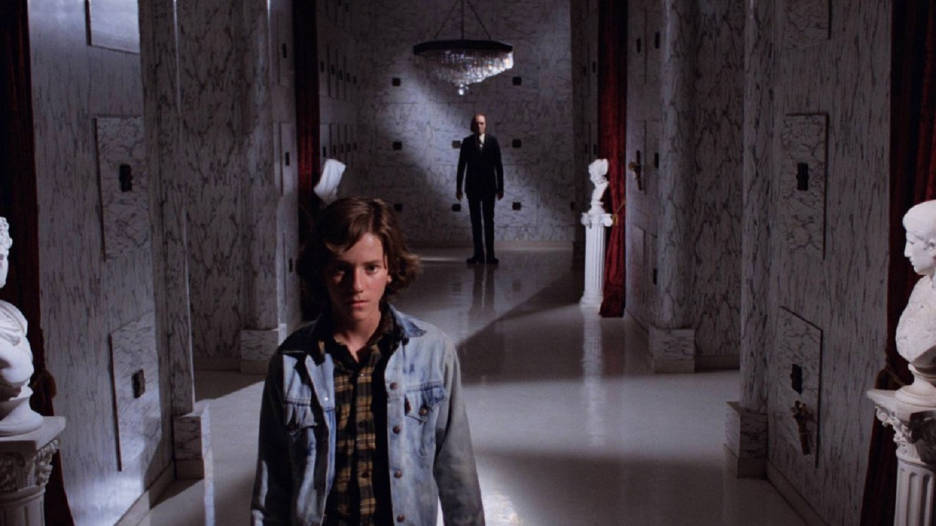 Young Michael Baldwin ventures into the Morningside Mortuary while The Tall Man (Angus Scrimm) lurks in the background in Phantasm (1979)