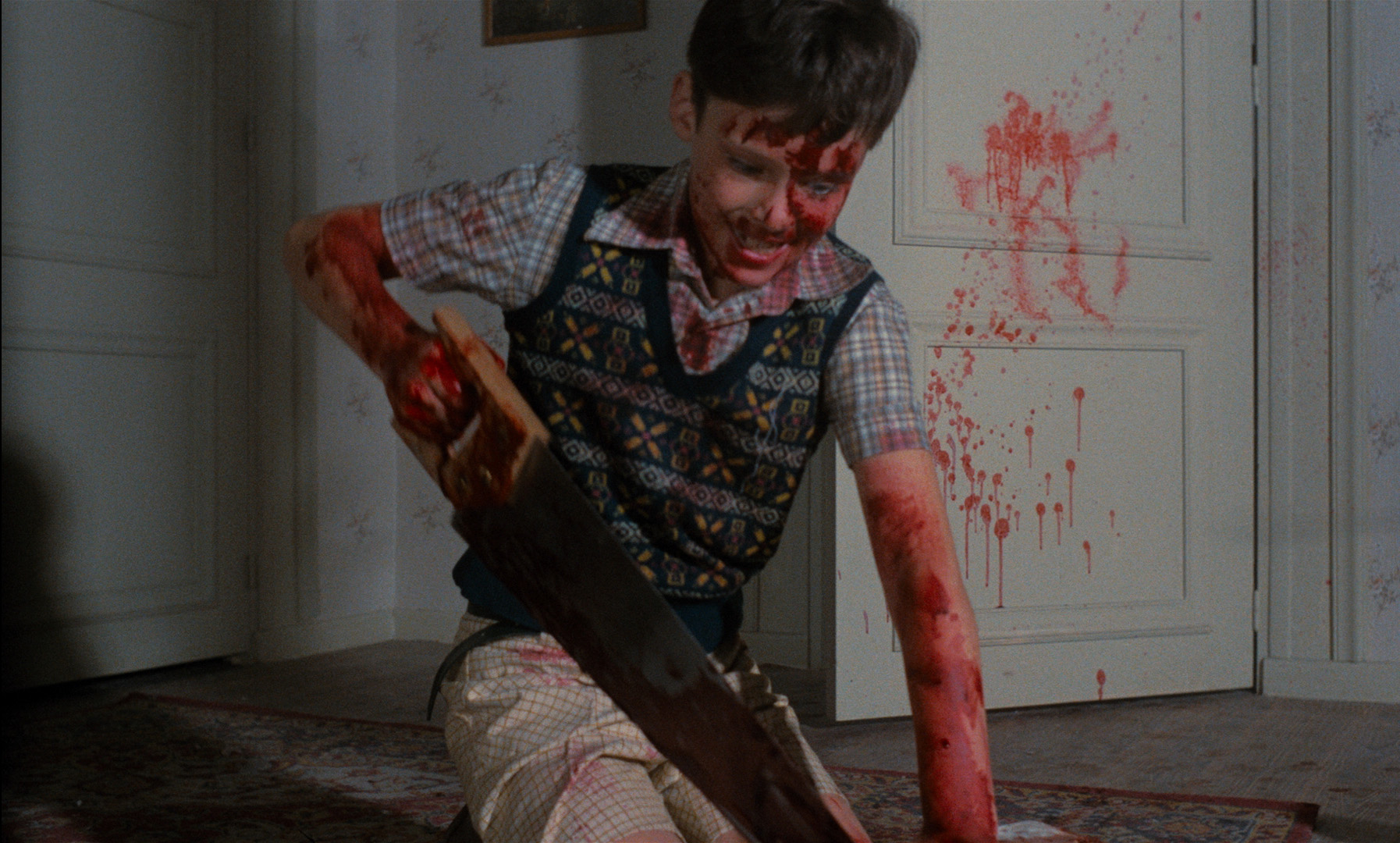 The young killer hacks up his mother's body in Pieces (1983)