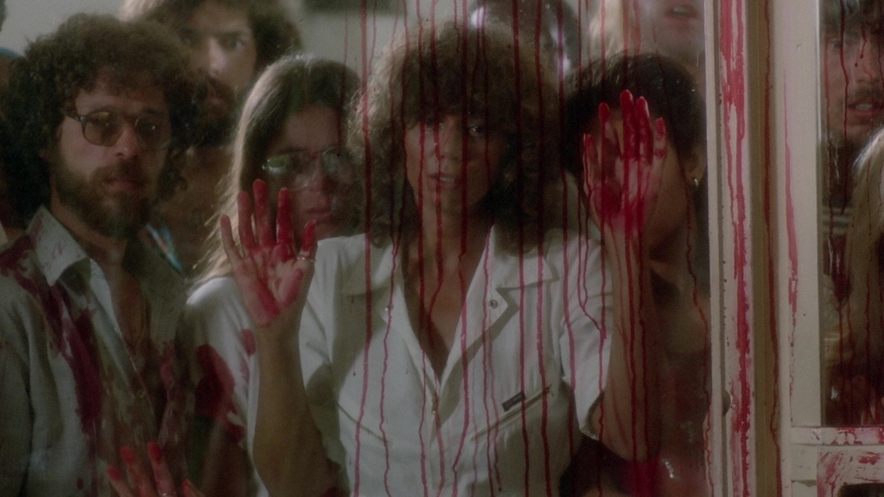 Tricia O'Neil looks on in the bloody aftermath of a piranha attack in Piranha II: Flying Killers (1981)