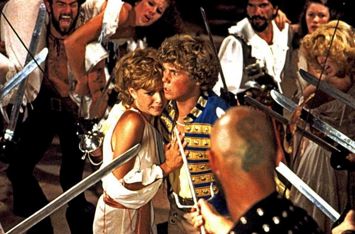 Kristy McNichol and Christopher Atkins surrounded by pirates in The Pirate Movie (1982)