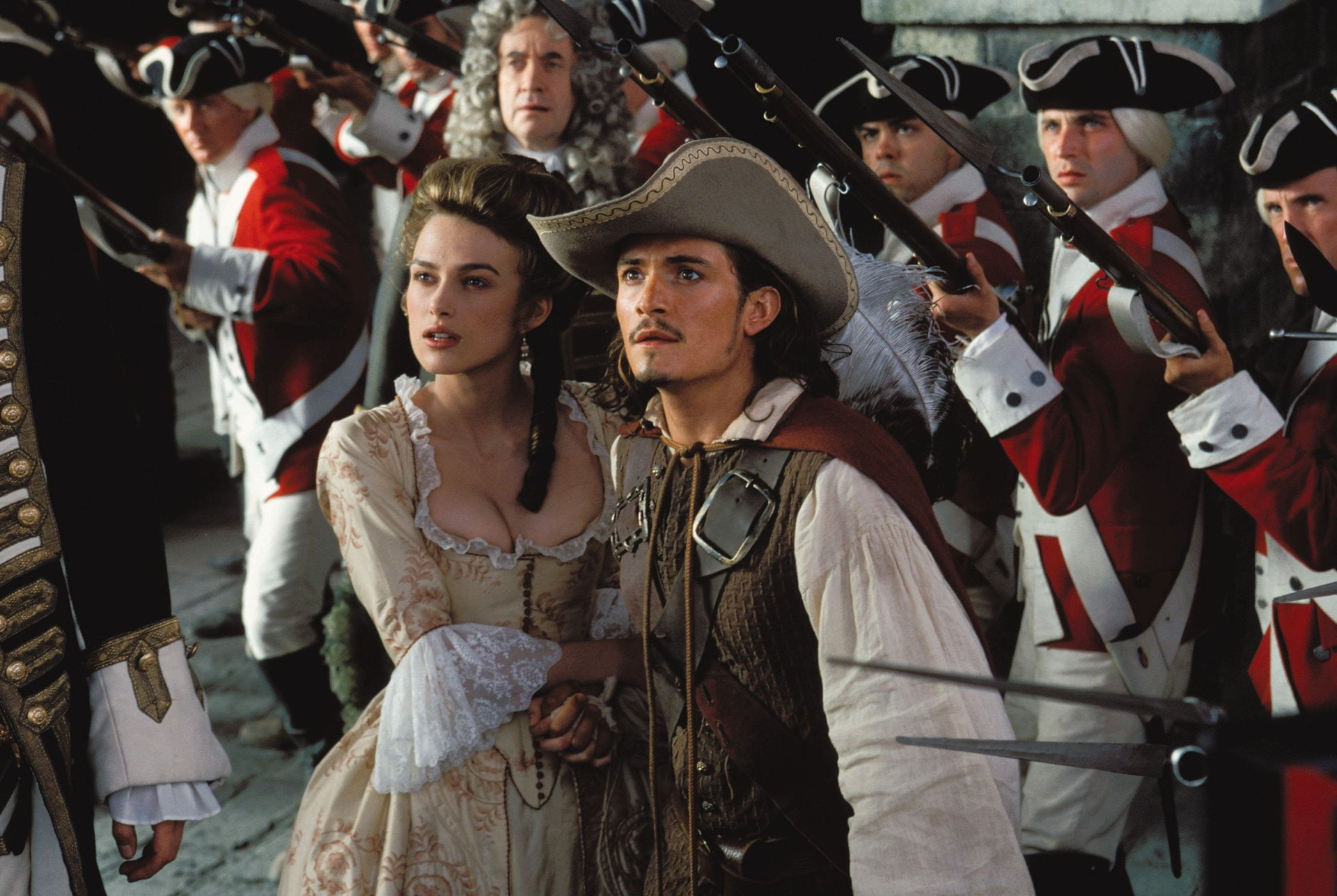 Elizabeth Swann (Keira Knightley) and Will Turner (Orlando Bloom) with the British Navy and Governor Swann (Jonathan Pryce) behind her in Pirates of the Caribbean: The Curse of the Black Pearl (2003)