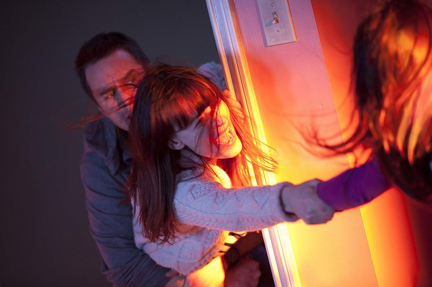 Parents Sam Rockwell and Rosemarie DeWitt try to save Kennedi Clements as she is dragged into the cupboard in Poltergeist (2015)