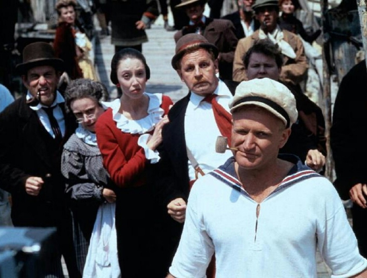 Popeye (Robin Williams) (front right) with Wimpy (Paul Dooley) and Olive Oyl (Shelley Duvall) to his left in Popeye (1980)