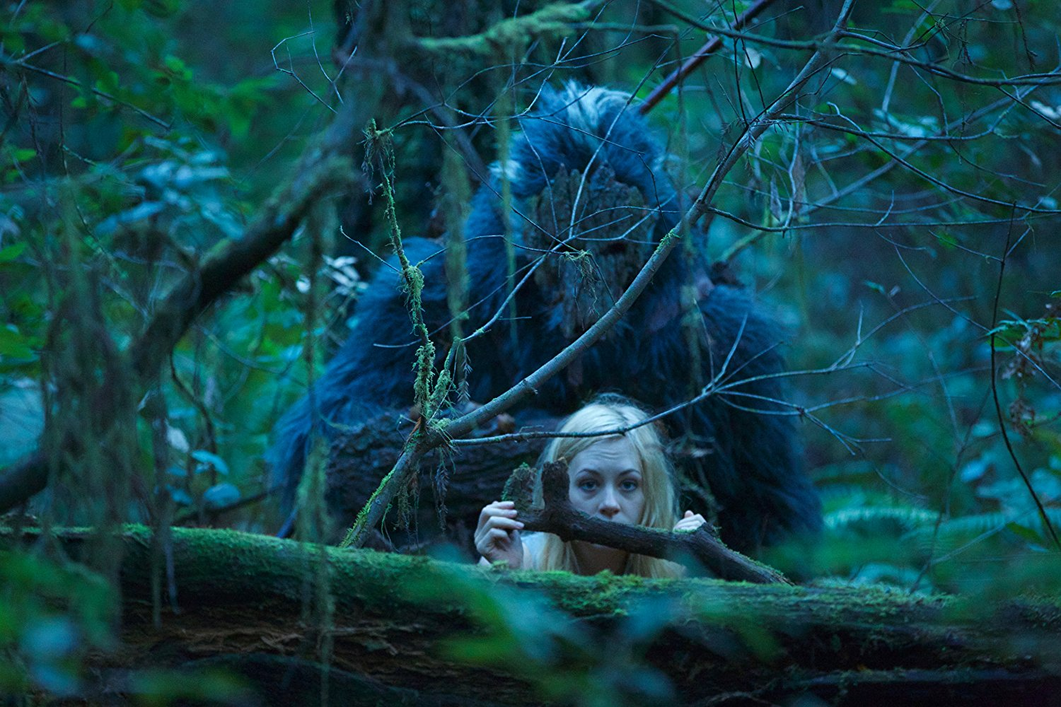 Casey Gagliardi hides in the woods as Bigfoot lurks unseen behind her in Primal Rage (2018)
