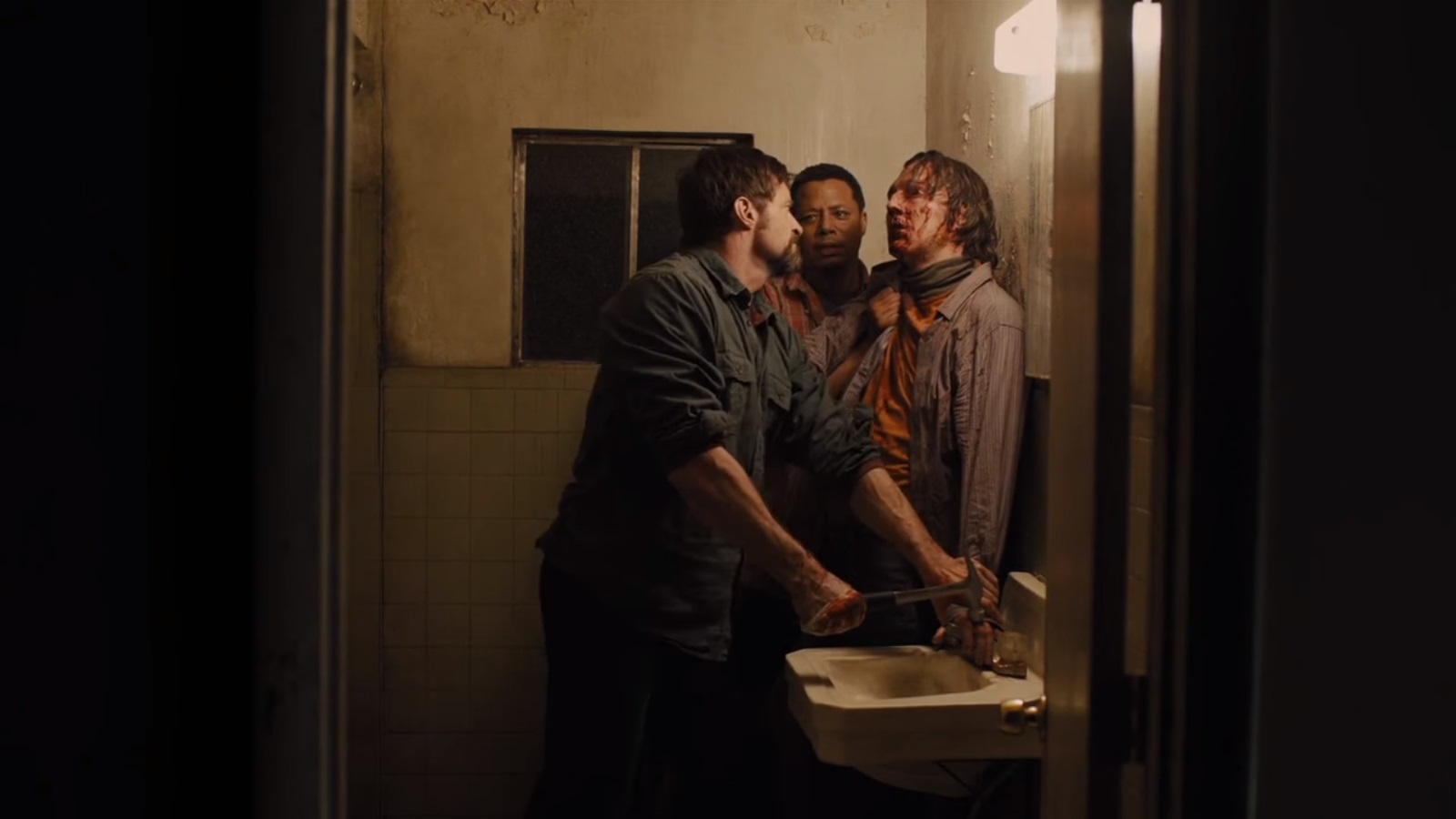 Hugh Jackman, along with Terrence Howard, prepares to torture Paul Dano with a hammer in Prisoners (2013)