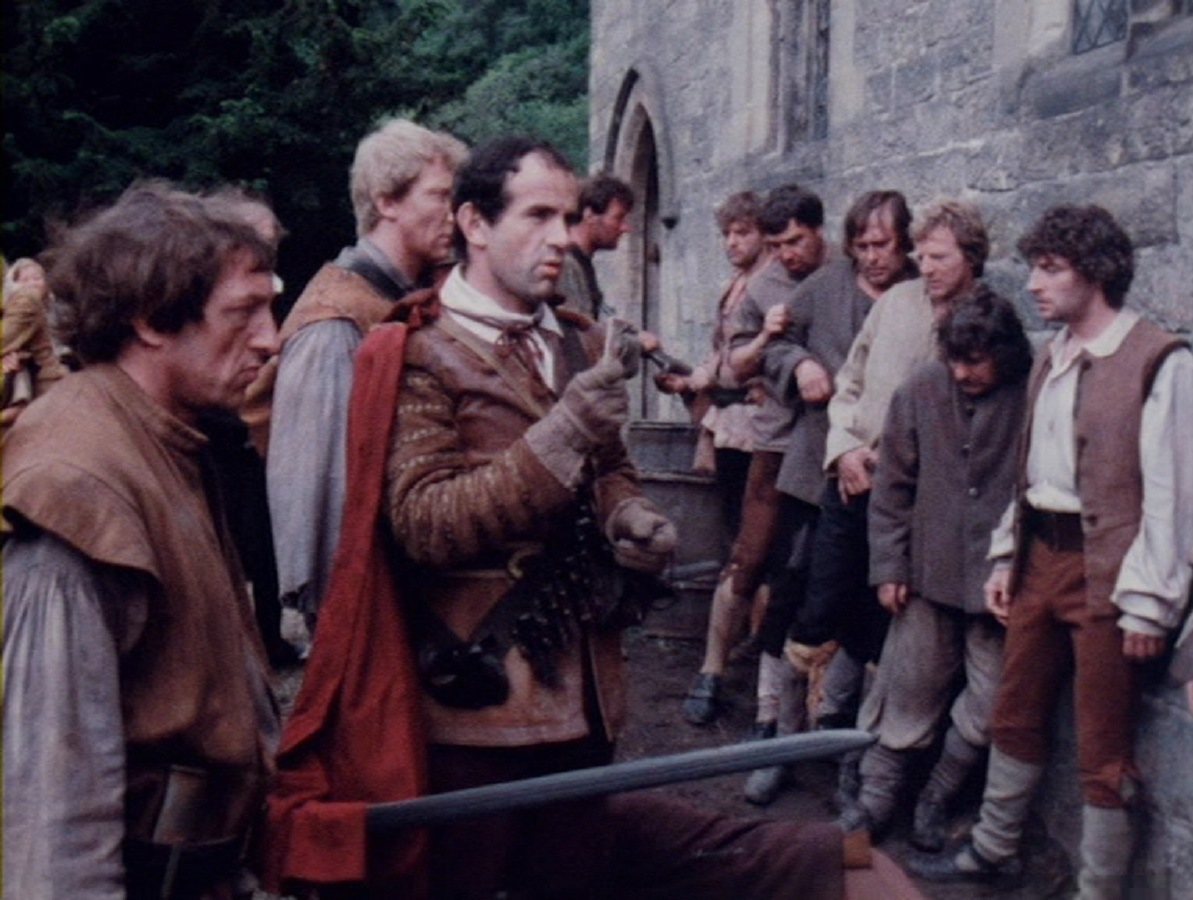 The villagers under siege from Royalist troops in Red Shift (1978)