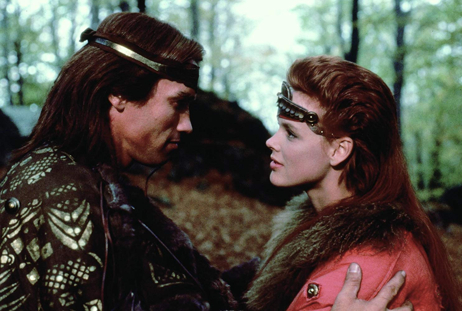 Red Sonja (Brigitte Nielsen) falls into the arms of Kalidor (Arnold Schwarzenegger) in Red Sonja (1985)