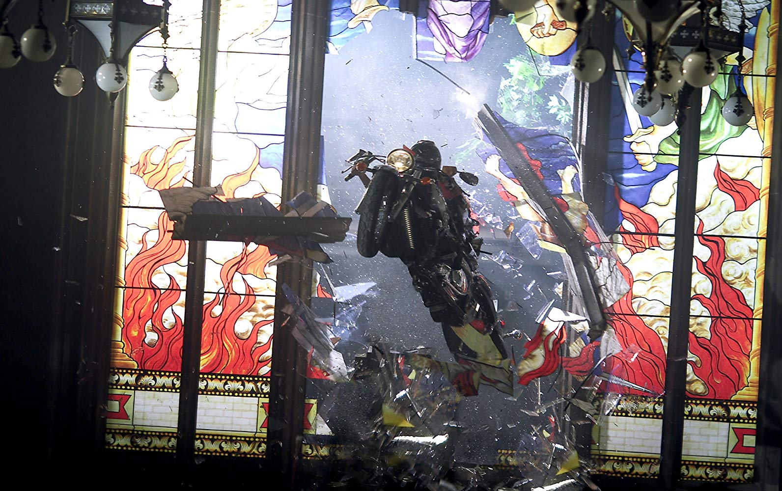 Alice (Milla Jovovich) rides a motorcycle through a stained glass window in Resident Evil: Apocalypse (2004)