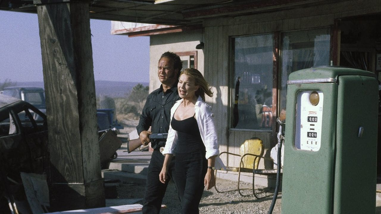 Jame Belushi holds hostage negotiator Kylie Travis at gunpoint in Retroactive (1997)