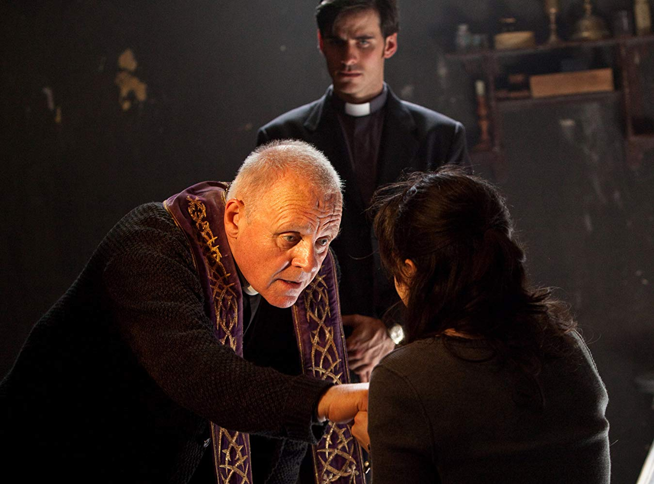 Anthony Hopkins performs the exorcism ritual with Colin O'Donoghue in the background in The Rite (2011)
