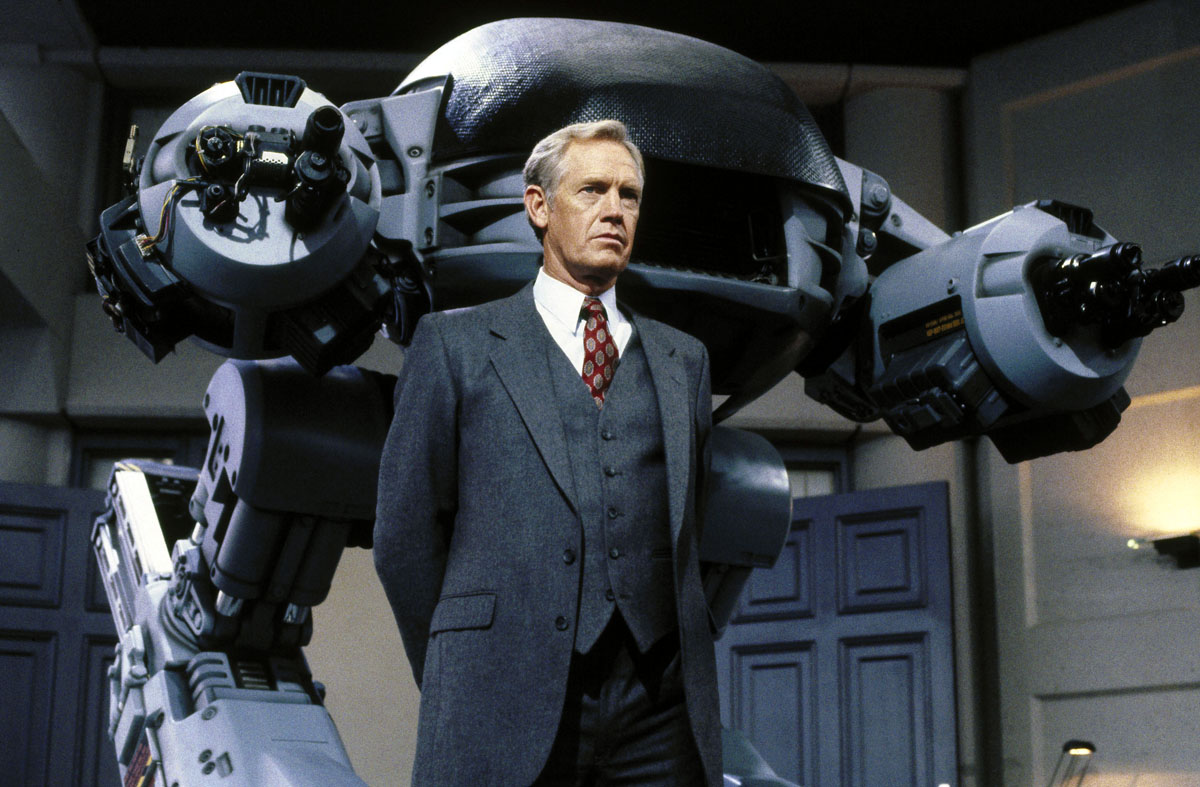 Dan O'Herlihy as The Old Man, flanked by the ED-209 in Robocop (1987)