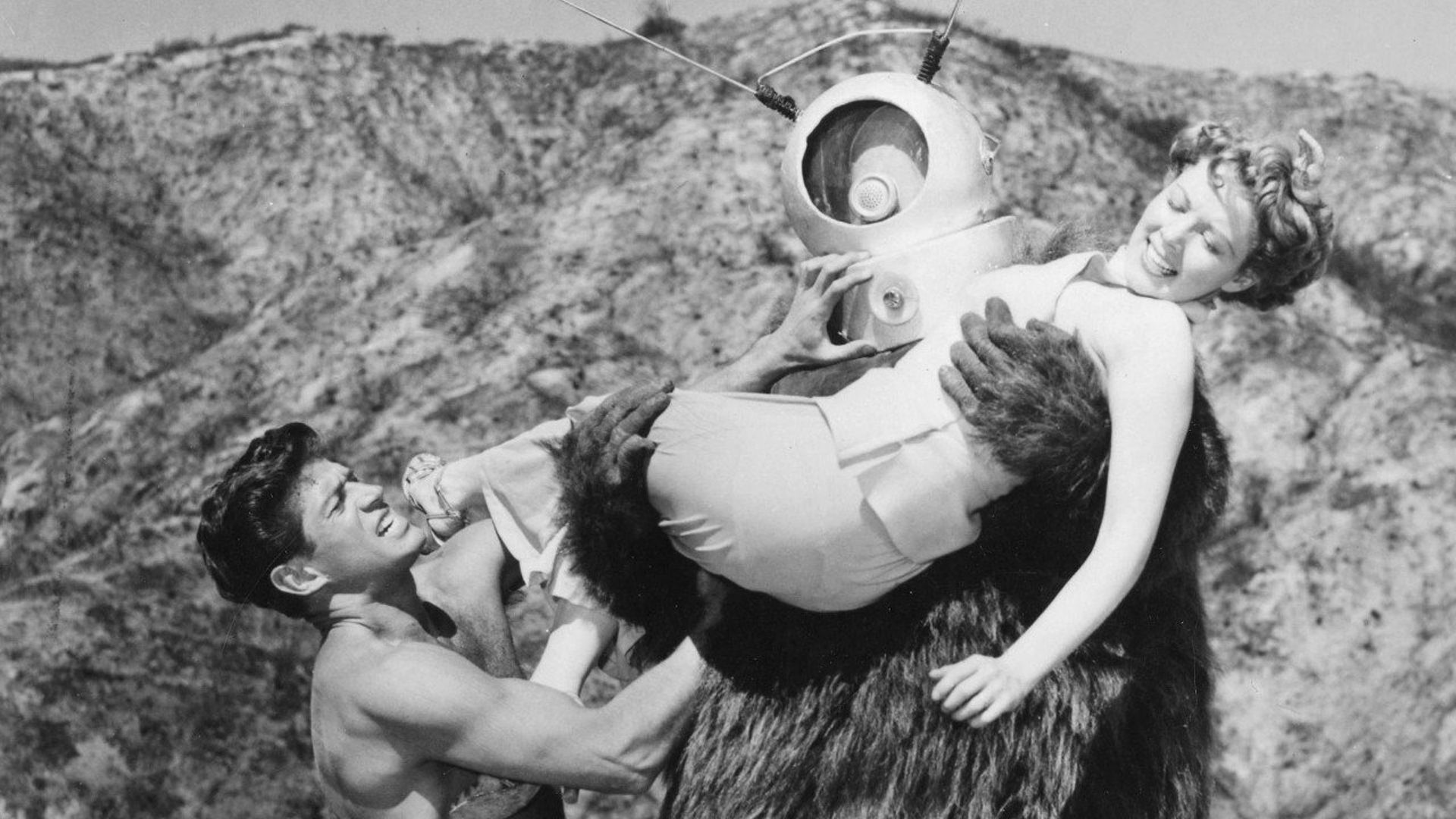 George Nader tries to stop Ro-Man (George Barrows) from abducting Claudia Barrett in Robot Monster (1953)