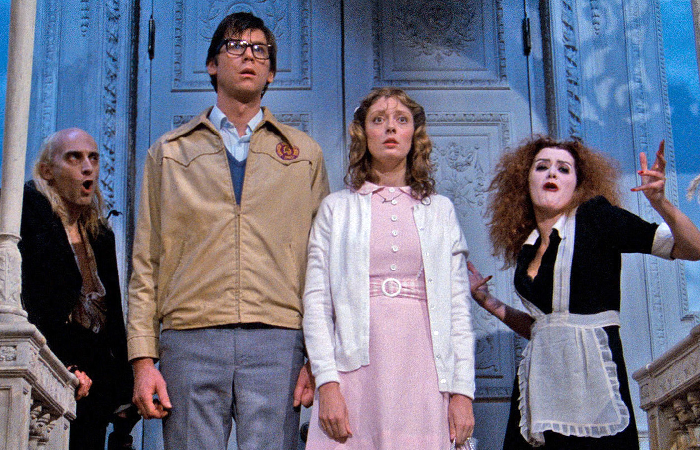 Newlywed innocents Brad and Janet Majors (Barry Bostwick and Susan Sarandon) (c) enter the castle flanked by the retainers Riff-Raff (the original play's creator Richard O'Brien) (l) and Magenta (Patricia Quinn) (r) in The Rocky Horror Picture Show (1975)