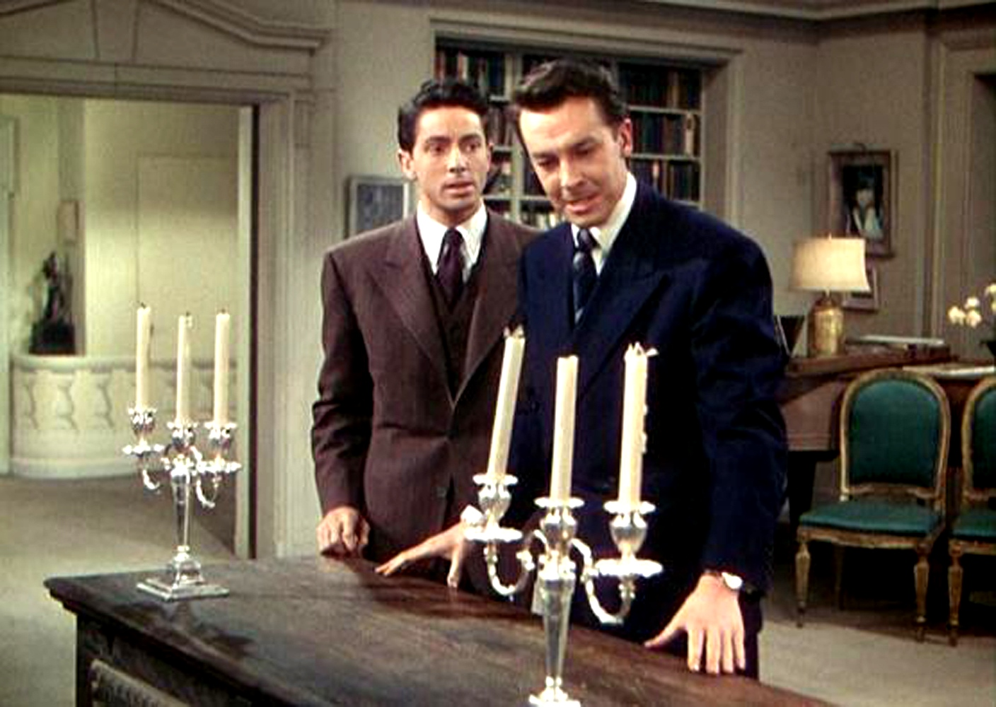 Farley Granger and John Dall prepare a dinner party using the chest containing a murdered body as the dinner table in Rope (1948)