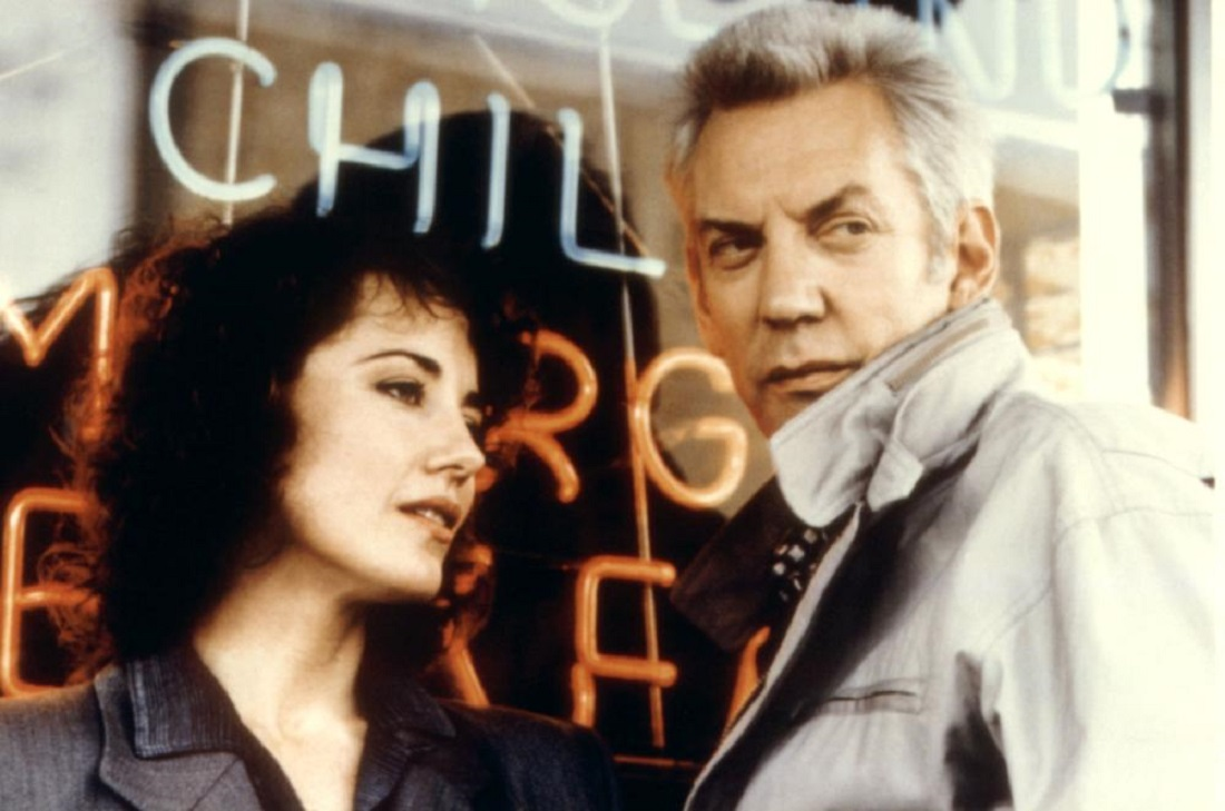 Journalist Belinda Balaski and Catholic priest Donald Sutherland team up to stop a killer in The Rosary Murders (1987)