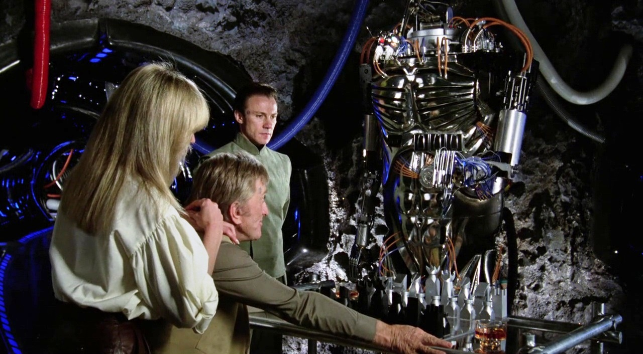 (l to r) Alex (Farrah Fawcett) and Adam (Kirk Douglas) sit down to play chess as Benson (Harvey Keitel) unveils his robot Hector  in Saturn 3 (1980)