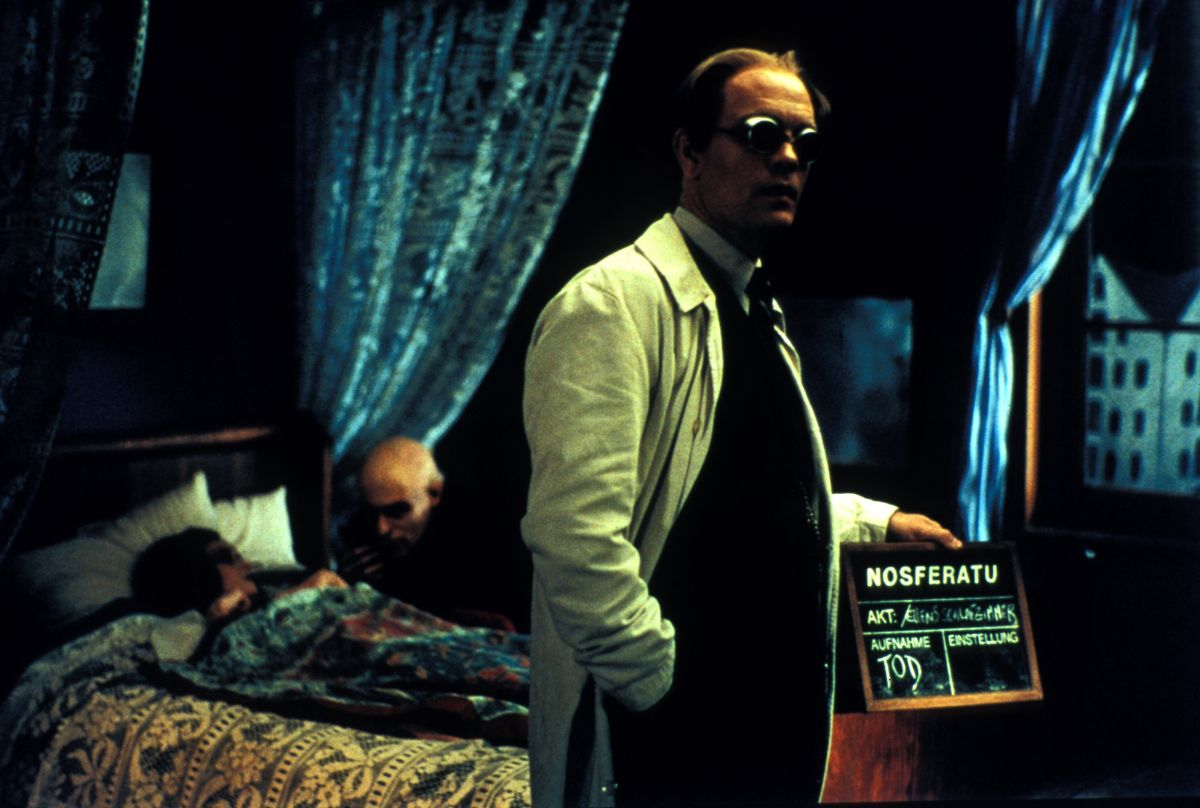 John Malkovich as F.W. Murnau (front) directs while Willem Dafoe's Max Schreck feeds on leading lady Catherine McCormack in the background in Shadow of the Vampire (2000)