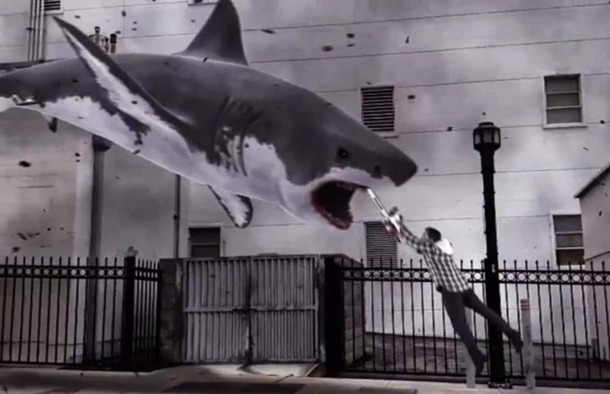 Ian Ziering armed with chainsaw launches himself into the gullet of an oncoming shark in Sharknado (2013)