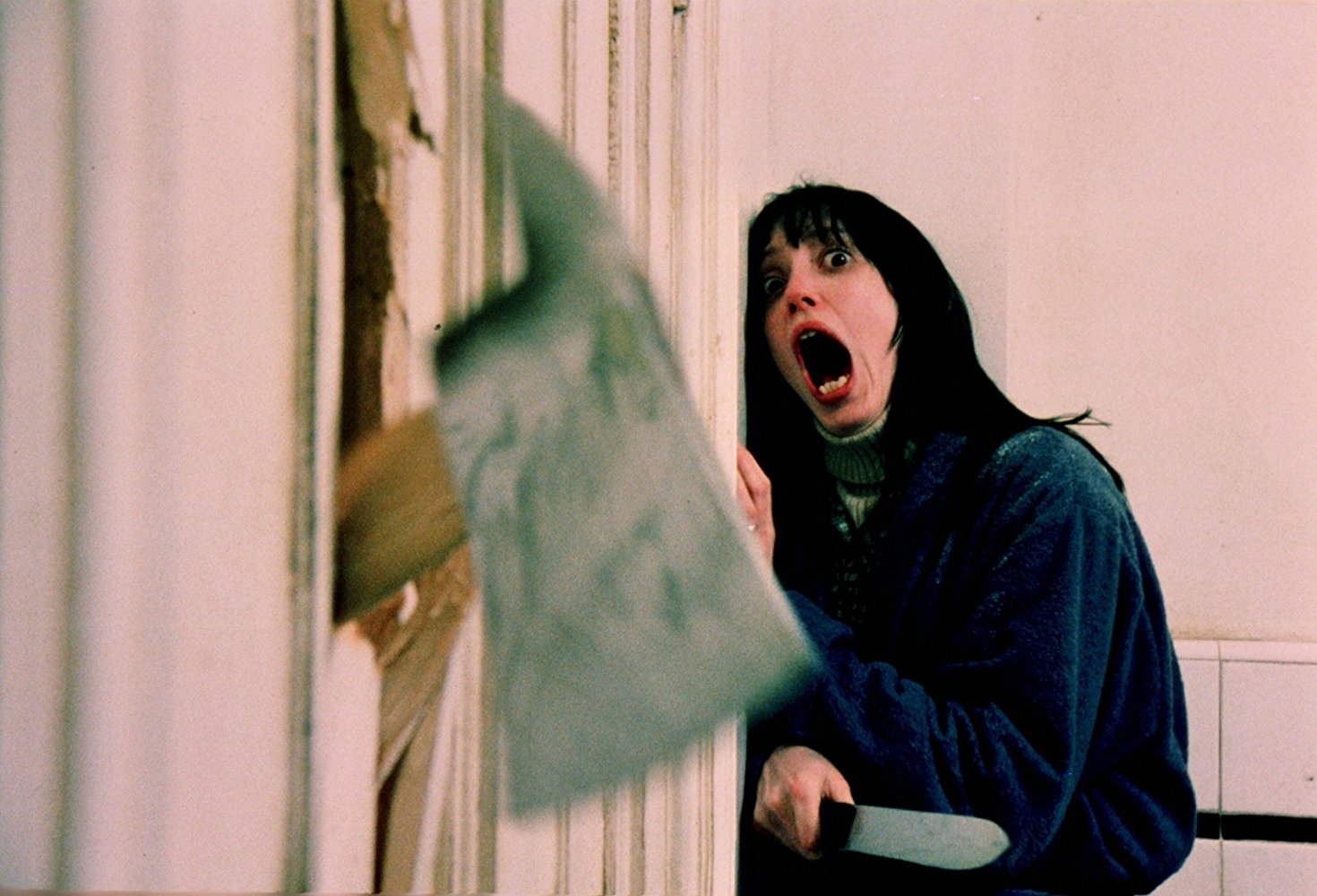 Shelley Duval facing an axe through the door in The Shining (1980)
