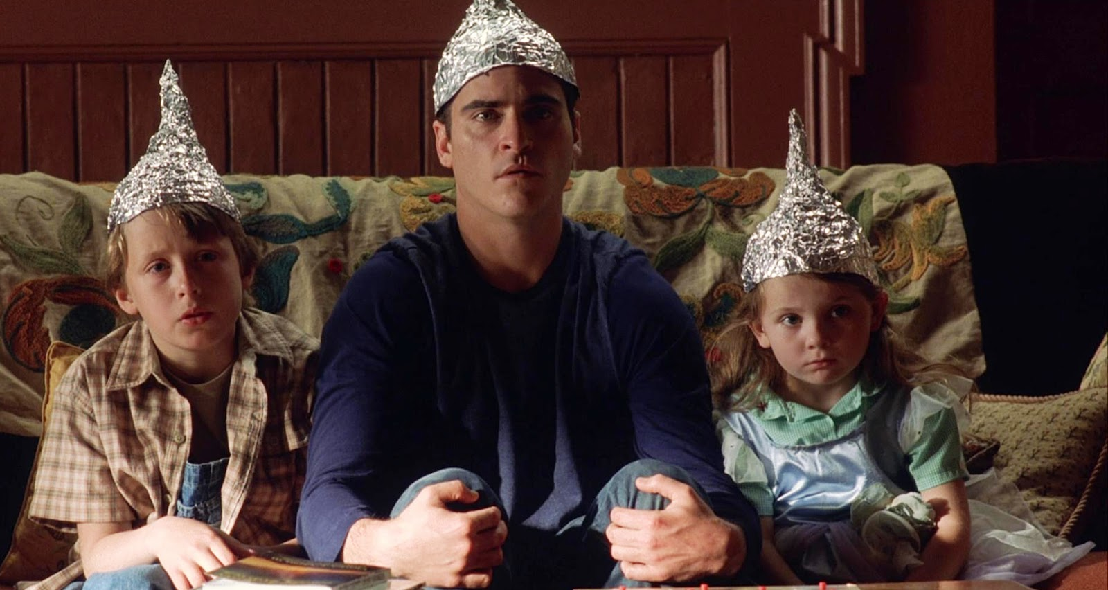 Joaquin Phoenix and the two children Rory Culkin and Abigail Breslin greet the phenomenon with aluminium hats in Signs (2002)