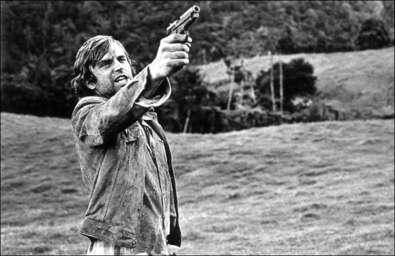 Smith (Sam Neill) shoots back at the pursuing Specials in Sleeping Dogs (1977)
