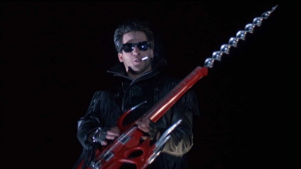 Alanas Hitch as The Driller Killer with combination electric guitar/powerdrill in Slumber Party Massacre II (1987)