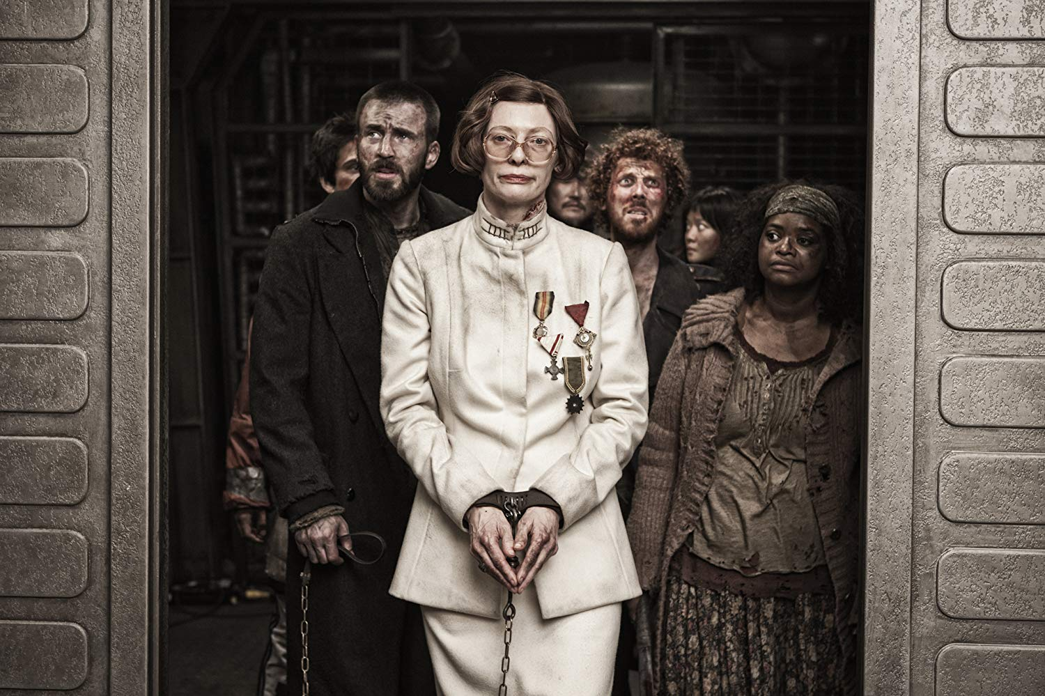 The revolutionaries - Chris Evans, Ewen Bremner, Ko Asung and Octavia Spencer - head to the forward compartments with an imprisoned Minister Mason (Tilda Swinton) in Snowpiercer (2013)