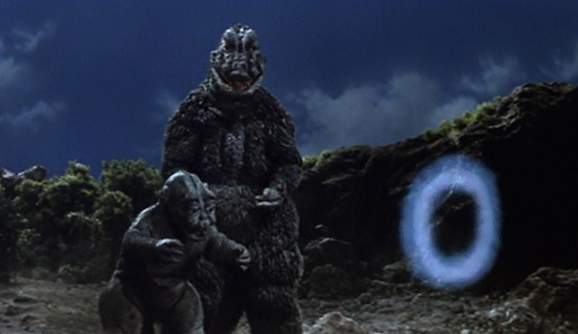 Godzilla with son Minya who finds he can only blow smoke rings instead of radioactive fire in Son of Godzilla (1968)