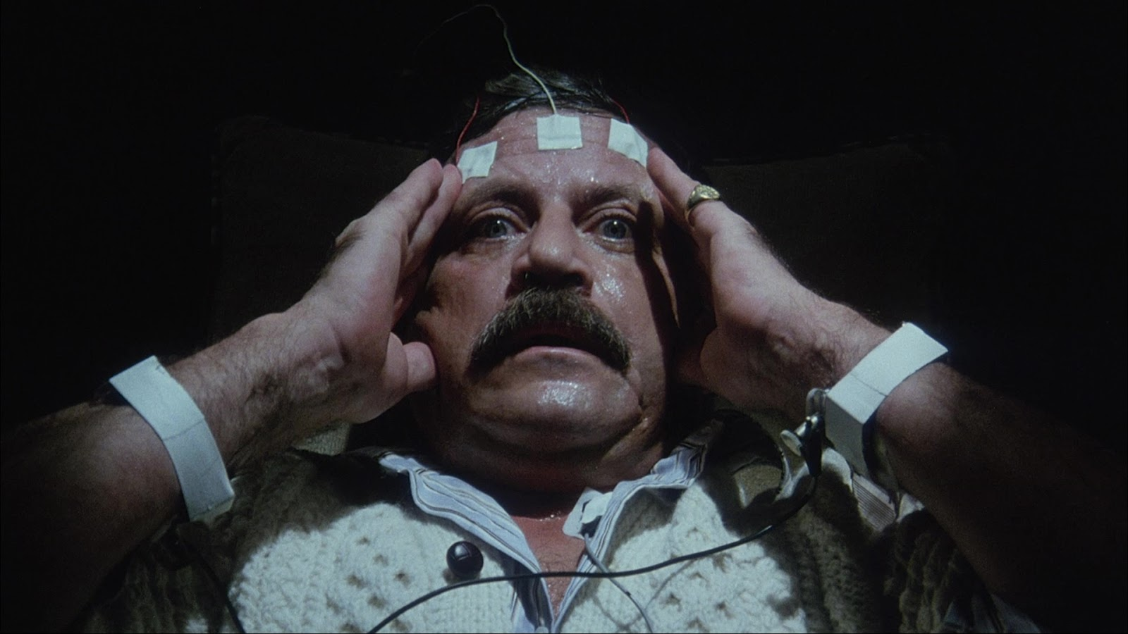 Billionaire Oliver Reed develops a psychic link with a giant snake in Spasms (1983)
