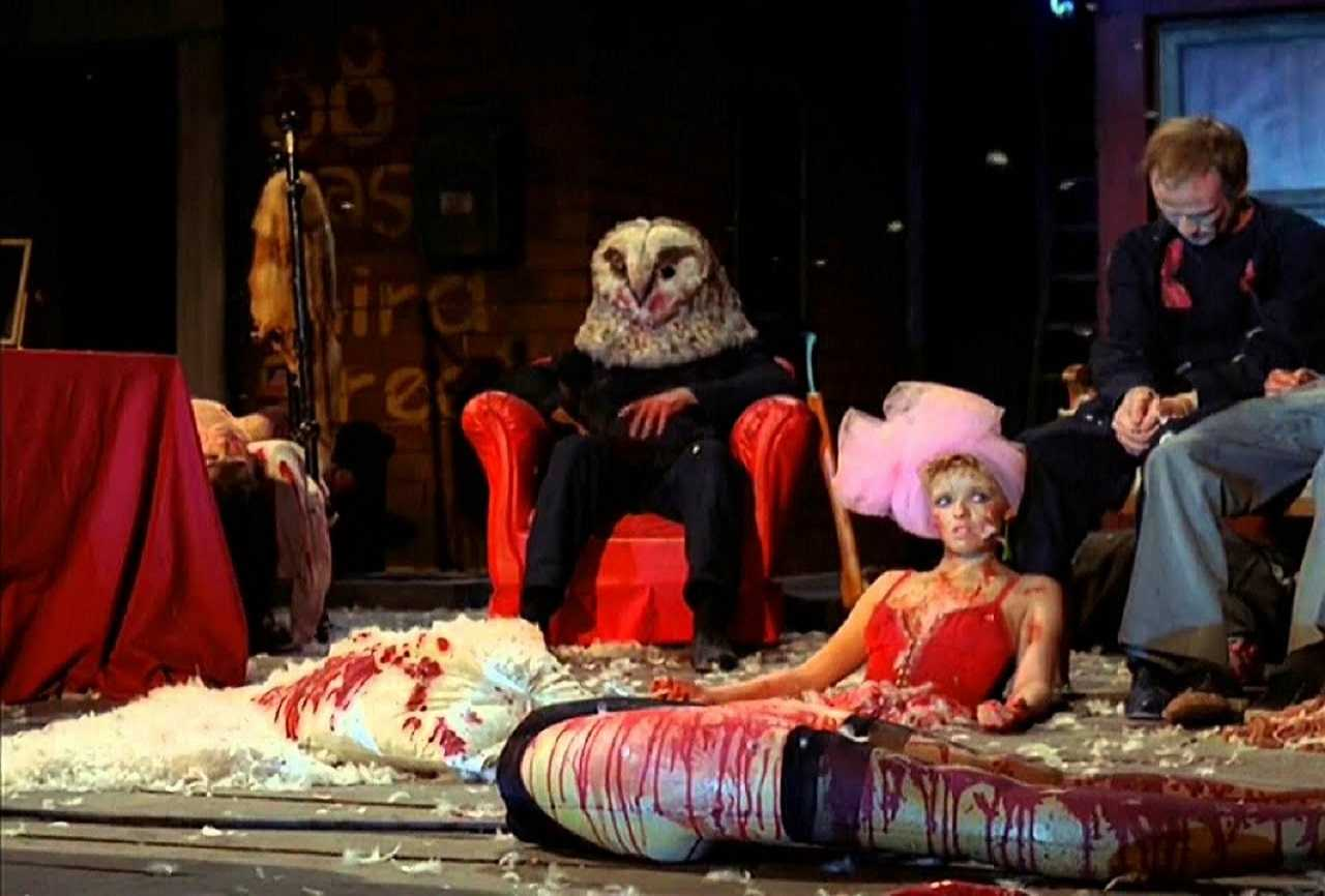 The owl-masked killer sits amid a stage filled with dead bodies in StageFright - Aquarius (1987)