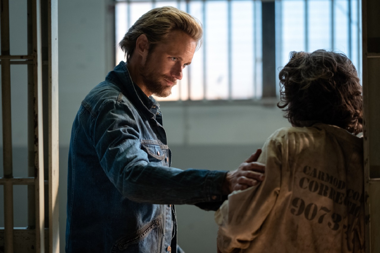 Randall Flagg (Alexander Skarsgård) greets Lloyd Henried (Nat Wolff) in jail in The Stand (2020-1)