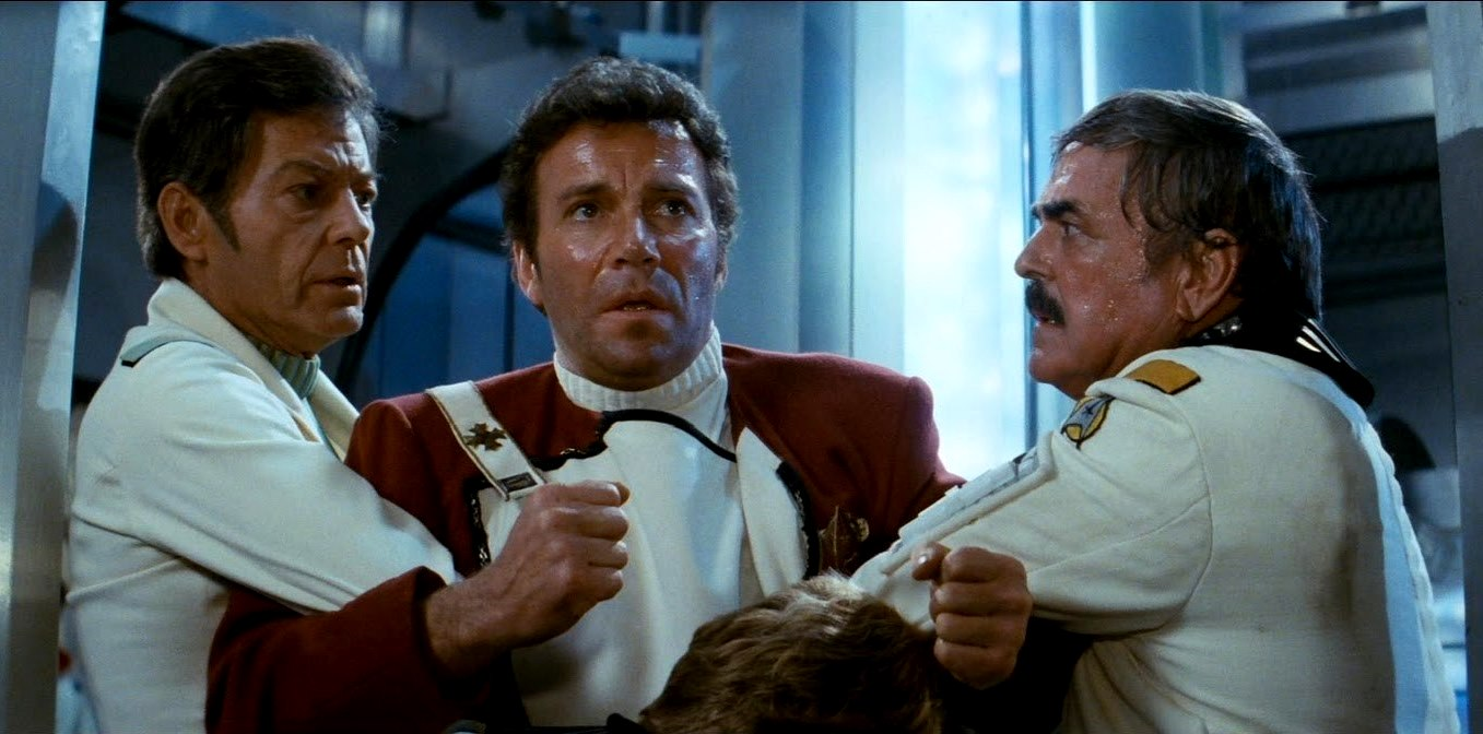 A distraught Captain Kirk (William Shatner) is restrained by Dr McCoy (DeForest Kelley) and Mr Scott (James Doohan) in Star Trek II: The Wrath of Khan (1982)